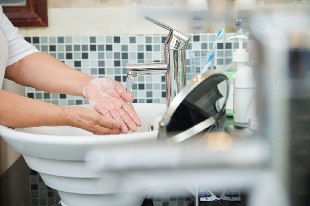 A close up of a senior woman washing her hands under the running water of her home's bathroom sink