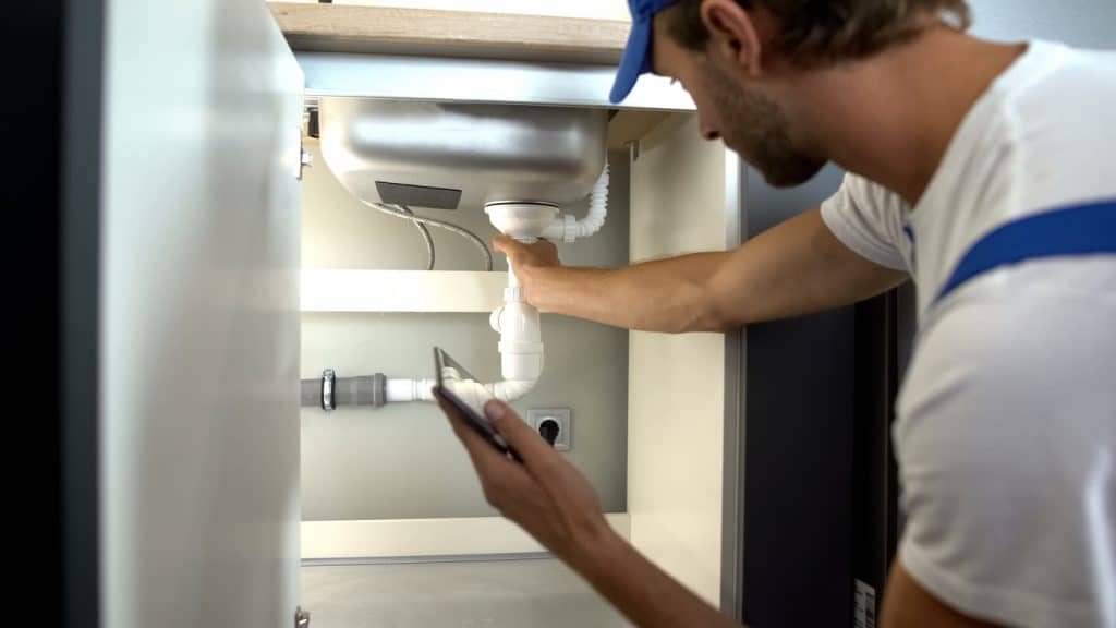 Professional plumber checking the drains and pipes of a residential property.