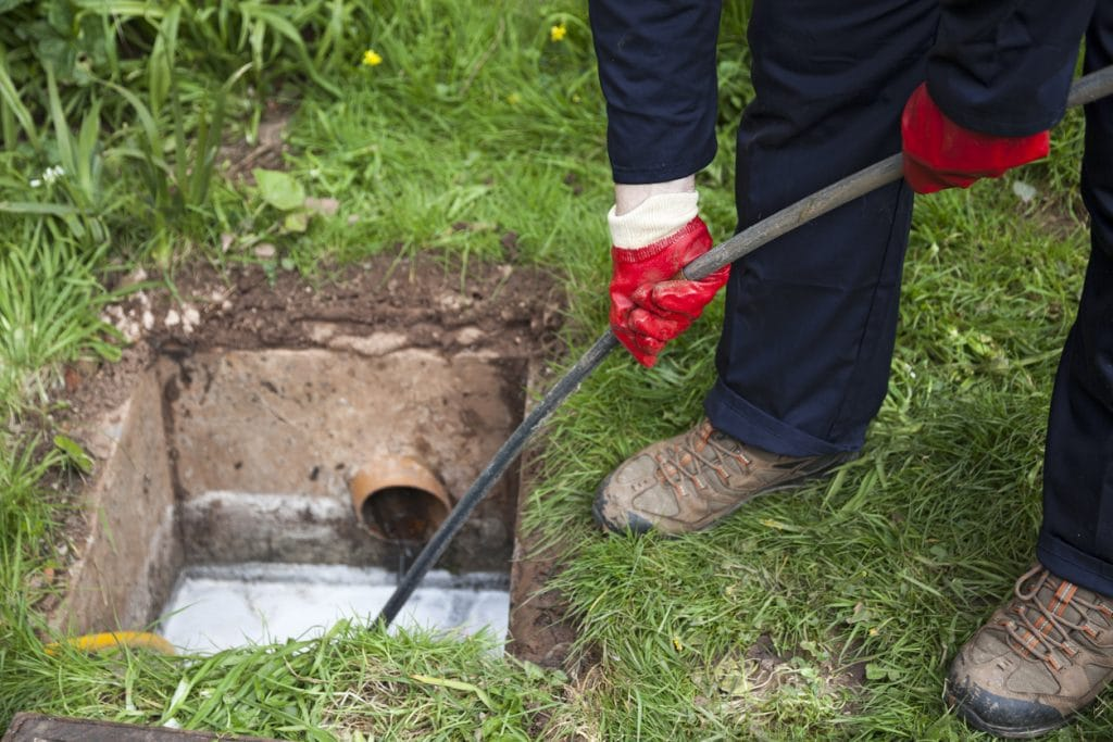 Professional male plumber unblocking a residential home's sewer line system.